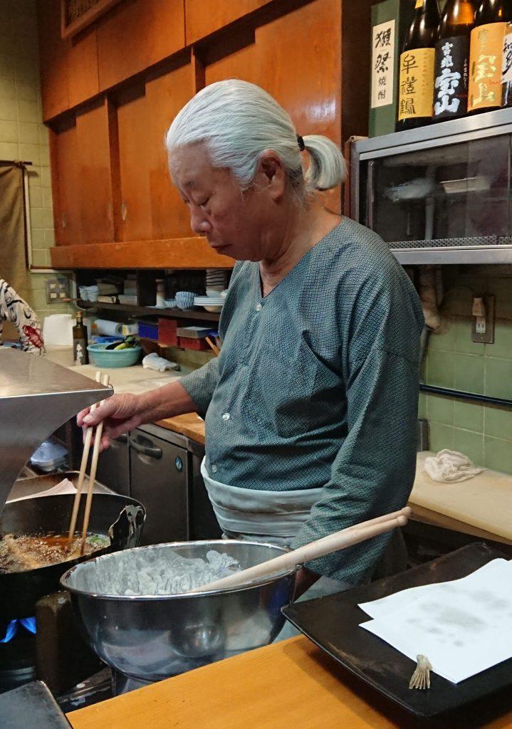 Tempura master frying a dish